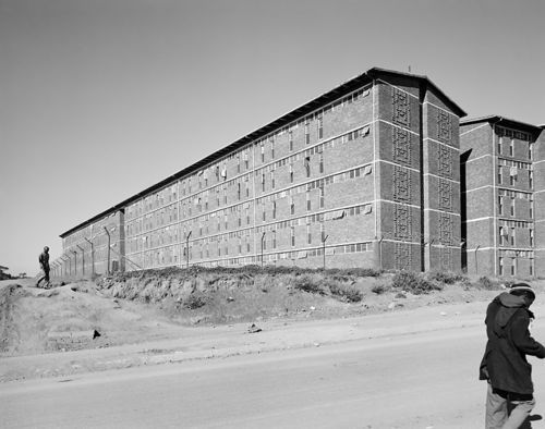 "David Goldblatt, TJ. ""Men walk past the south-east wing of a hostel for Black male workers, erected during apartheid as part of a scheme to make Joburg city and suburbs 'White', Alexandra Township, 1 June 1988."""