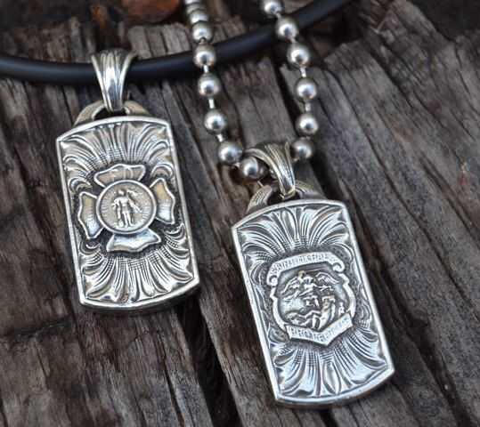 """To honor and protect our men and women in uniform, Rockin Out has created an awesome Sterling Silver engraved dog tag bearing the St. Florian for firefighters and the St. Michael for our police force. Each dog tag will come standard with a 24"""" stainless steel ball chain necklace or you can upgrade to a 4mm 18"""" or 20"""" black rubber necklace with a Sterling Silver clasp for $10 extra. These pendants can be ordered on our site for $49."""