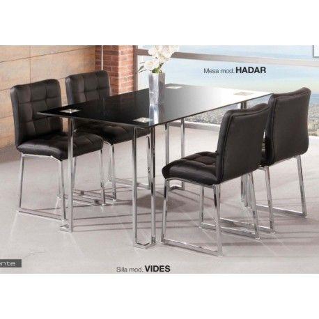 Conjunto de mesa con cuatro sillas para salón comedor o cocina Vides-Hadar. Está compuesto de mesa metálica con tapa de cristal templado de 8mm en blanco o negro con estructura metálica con recubrimiento cromado con cuatro sillas metálicas tapizadas.