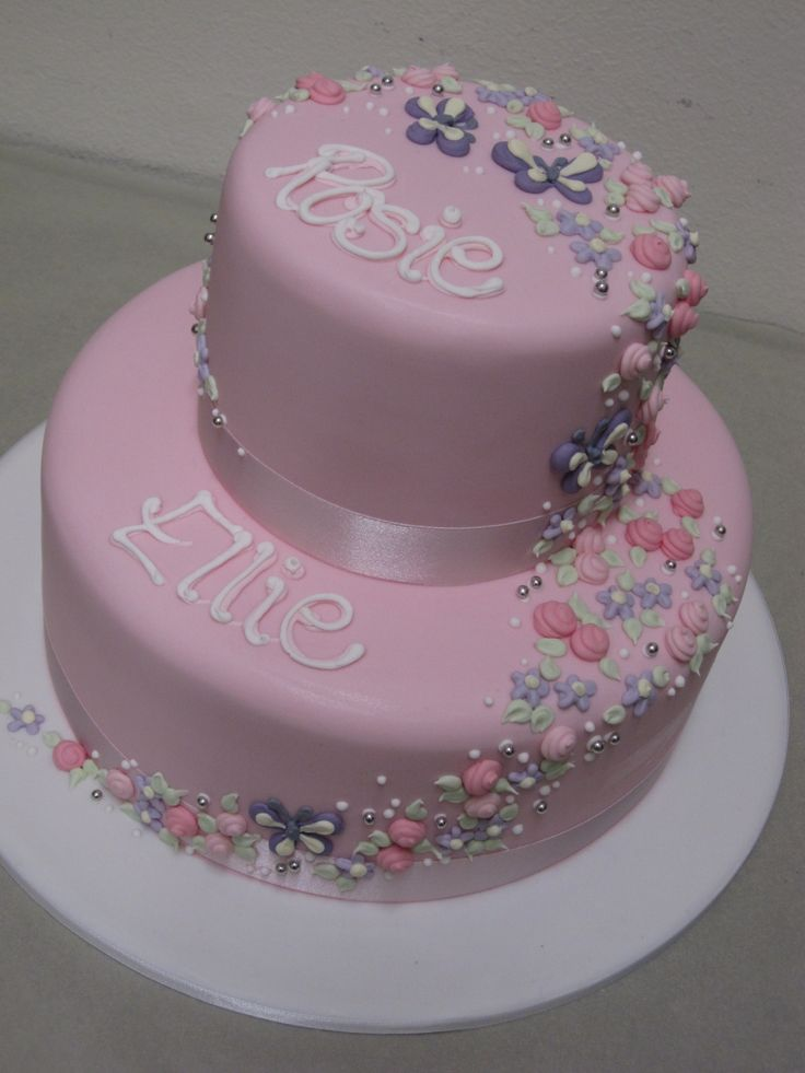 a two tier cake for two little girls with piped on flowers and butterflies cascading down