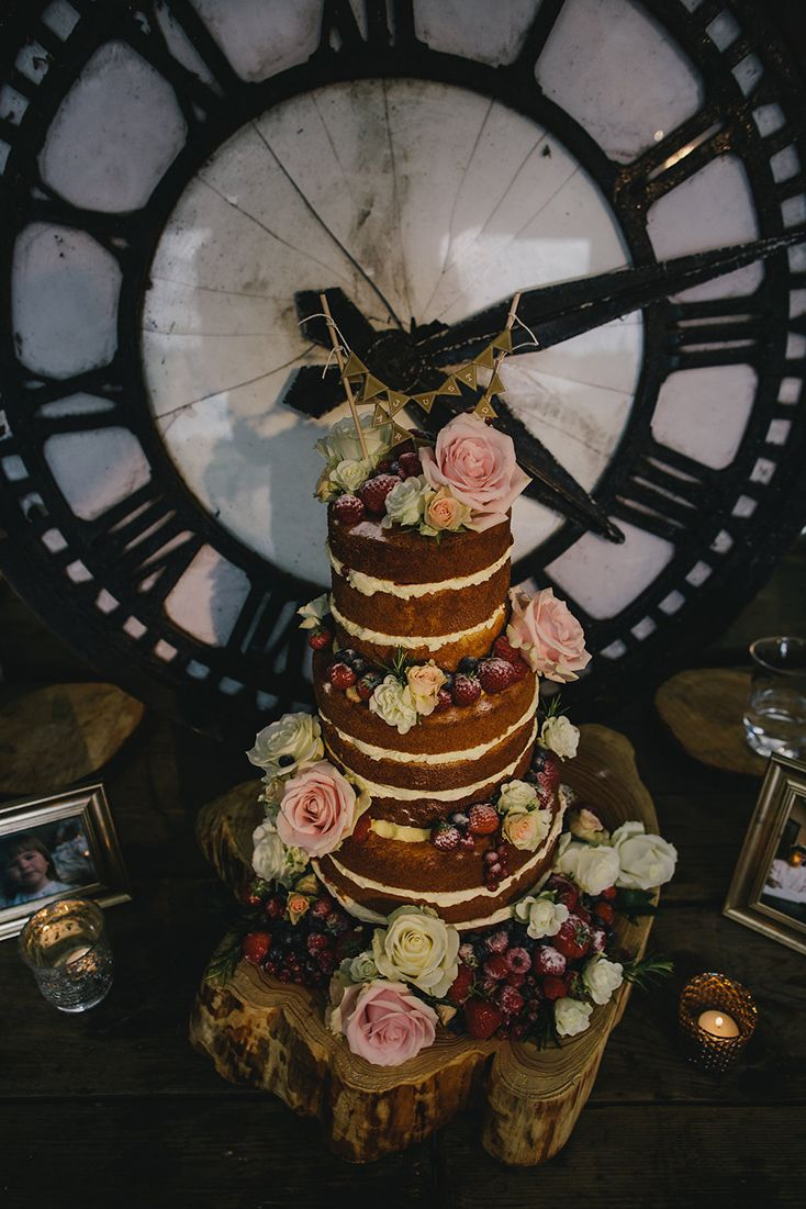 Scrumptious naked wedding cake rustic berries flowers log base wooden.    Image ©️ Marshal Gray Photography