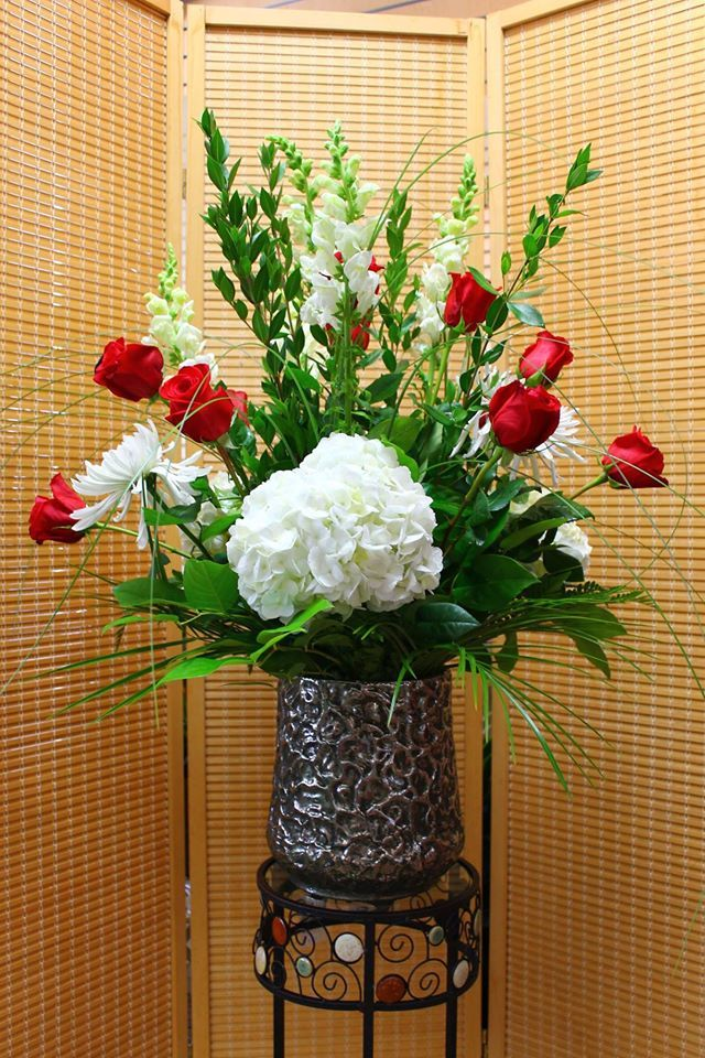 Gorgeous Hydrangea centerpiece with red roses in a stunning vase! Come get this arrangement today!