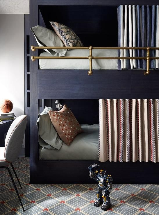 Contemporary blue boys' room features a dark blue bunk bed fitted with a brass plumbing pipe safety rail as well as short curtains dressed in pale gray bedding.