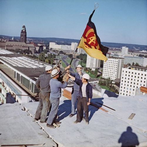 After completing a new building, East German construction workers hoist their national flag over their latest masterpiece.