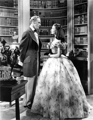 Scarlett and Ashley in the library at Twelve Oaks. Scarlett is 16 and Ashley is 21. In real life both actors were much older. Vivien Leigh was 25 and Leslie Howard was 45. He wore heavy makeup and a hairpiece to make him look younger.