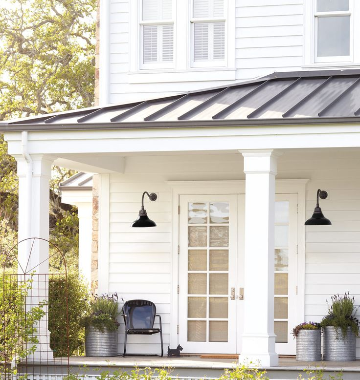 Metal roof, lanterns and ohhh the planters too! Is there anything more classic than a white house with black accents?