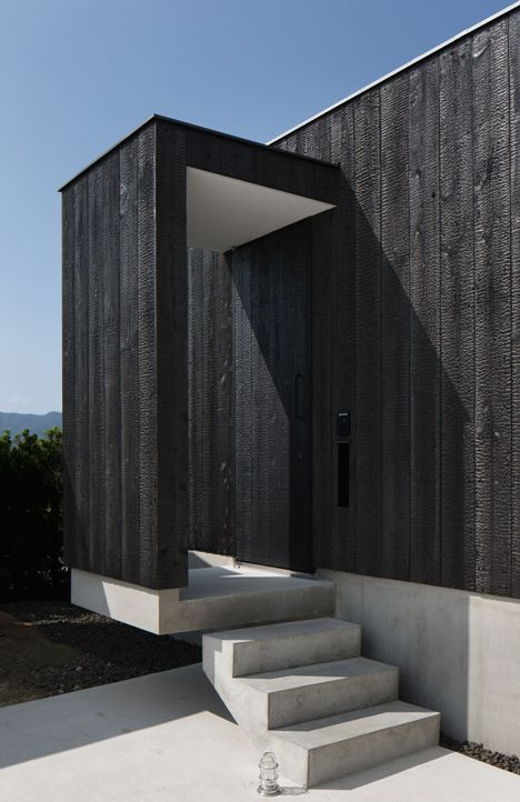 Technique japonaise du bois brûlé / Charred Japanese cedar clads the exterior of this split-level house.