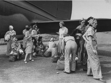 US Army nurses waiting to board cargo plane for transport after they were liberated from Japanese internment camps during WWII. Location:	Manila, Luzon, Philippine Islands
