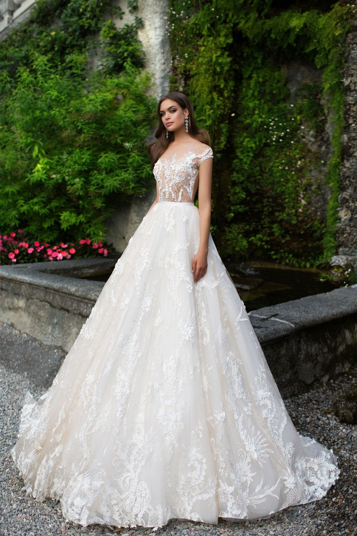 Charming wedding gown Annet with the play of milk and peach shades on a lush ball skirt. Gauzy bodice with the bateau neckline is decorated with a fine lace and delicate belt. On the back lace looks like the rime pattern in the winter window.