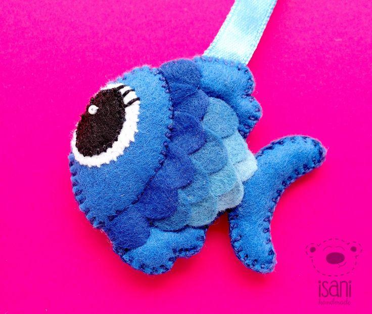 Breloczek z filcu Rybka. Projekt autorski. Rybka jest uszyta z odcieni niebieskiego filcu o grubości 1mm. Wypchana tak, że poszczególne części: płetwy, ogonek i buźka stanowią odrębne wypełnienie. Oczko z koralika. Całość zawieszona na wstążeczce. Wielkość 6,8 cm na 6,2.