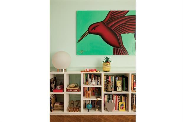 Reformas: 2 deptos antiguos renovados para brillar Una obra de la dueña de casa pende sobre un mueble de estantes decorado graciosamente con libros y adornos traídos de viajes.