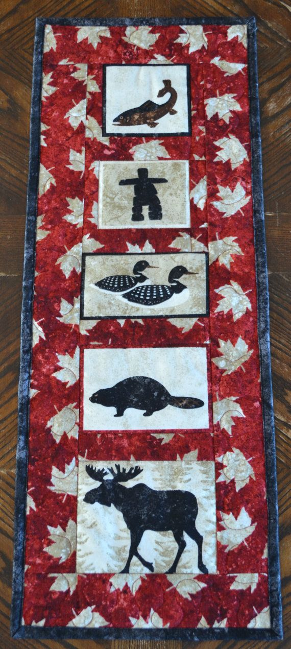 This Canadian Art Quilt Wall hanging will look great hanging on your wall or would be great as a hostess gift or souvenir gift! Canadian icons of Moose, Beaver, Loon, Salmon and Inukshuk are bordered with a vibrant red maple leaf print. Backed with coordinating prints (shown in 3rd photo) and bound with a charcoal black. All fabrics are top quality 100% cotton fabrics and made 100% by me, from piecing to final finishing!    Size: 9.5 x 25 (24cm x 63.5cm)  Please measure to be sure this quilt…