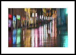 Colorful evening by Svetlana Iso.     Abstract bright blurred landscape with unidentified people, city street in rainy night. Vivid illumination and reflection in wet pavement of shop windows and street lamps. Active lifestyle  #SvetlanaIso #SvetlanaIsoFineArtPhotography #Photography #ArtForHome #InteriorDesign #FineArtPrints #Home #Gift #Color  #Rain