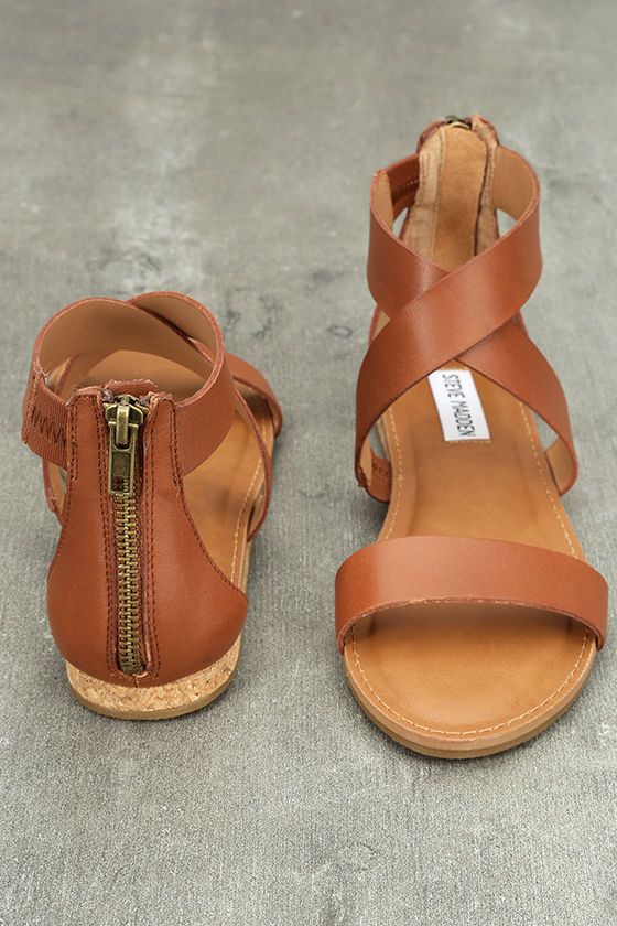 "Style, comfort, and more can be yours with the Steve Madden Halley Cognac Leather Sandals! Genuine leather straps shape a peep-toe upper with crisscrossing ankle straps creating a trendy gladiator design. 3.75"" heel zipper."