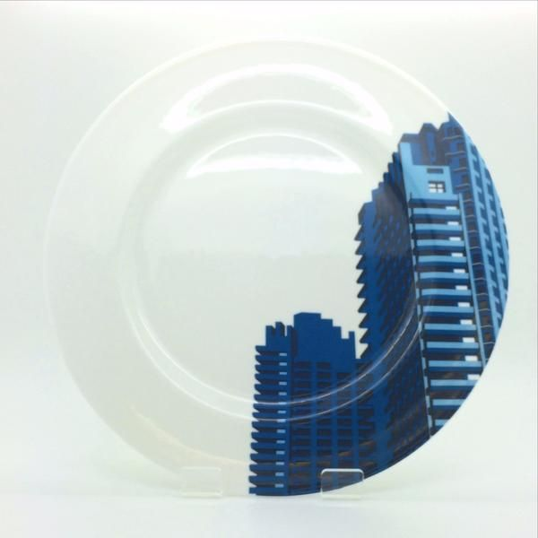 Barbican Shop Barbican Towers Plate By Dorothy: Dine from a fine bone china plate depicting the Barbican's iconic Brutalist architecture, created by Dorothy design studio. Featuring the instantly recognisable curved balconies from the Barbican Towers, this plate design includes a segment from the original print, which you can see here. Commissioned by the Barbican, these prints form part of a series of nostalgic travel prints celebrating the unique but often forgotten beauty of the grand…