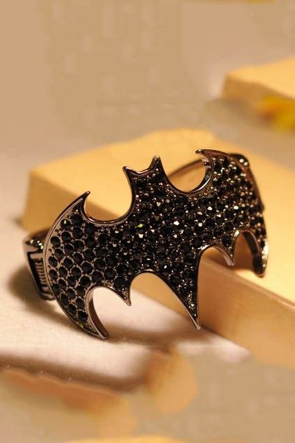Bracelet crafted in metal, featuring Batman logo the centre with black stones embellishment, with a clip fastening.$24