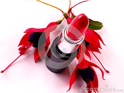 A closeup of a tube of red lipstick and  fuchsia flowers