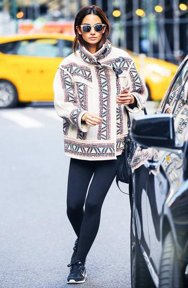Lily Aldridge wears a printed toggle coat with leggings, Ray-Ban sunglasses, and Nike sneakers