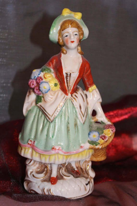 Occupied Japan Figurine Gorgeous figurine Woman with basket of flowers Measures approximately 6 1/2 tall Green hat with bow Red accent Green dress with flowers Occupied Japan Great addition to any collection Perfect gift idea for the holiday season, hostess gift, housewarming gift    I take great care to package and ship your vintage treasures in a secure and timely manner. These items are vintage and as such may have some wear and tear in prior use. Items will arrive cleaned.  See my ot...