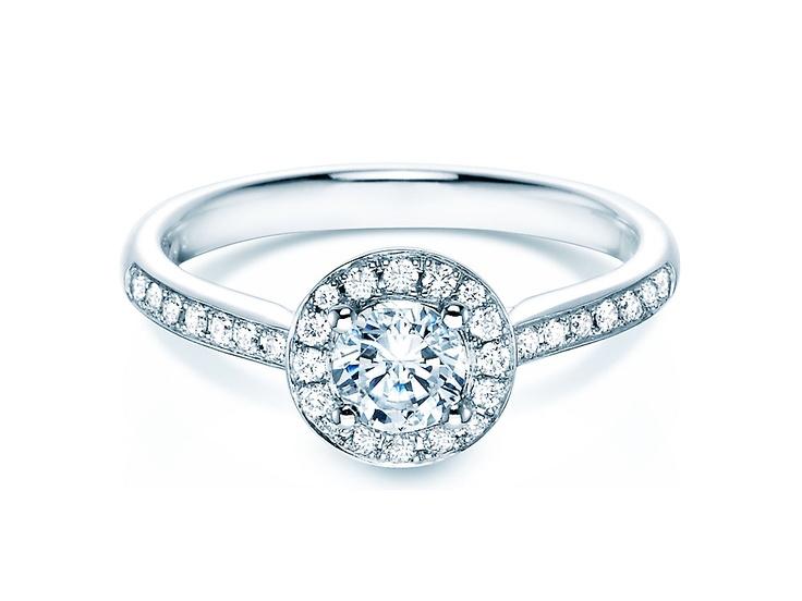 """Verlobungsring - Halo Der Begriff """"Halo"""" kommt aus dem englischen und bedeutet übersetzt """"Heiligenschein"""". Im übertragenen Sinn trifft dies auf die filigrane Diamantumrahmung zu, die den mittleren Brillanten betont."""