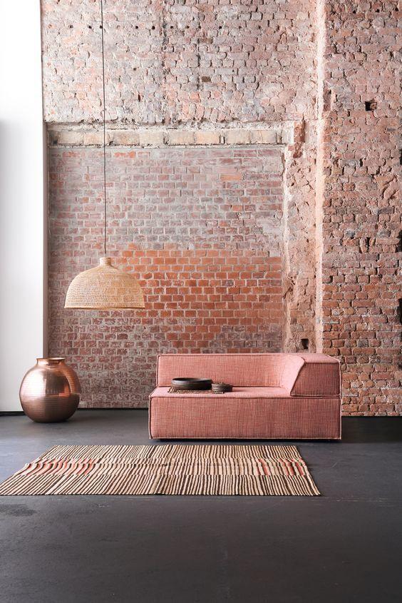 Le canapé rose de ce loft rappel les teintes rosacées du mur de briquettes