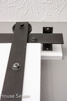 Barn Door Tutorial | DIY Barn Door Hardware | AWESOME use of garage door pulleys (cheap) and metal - just have to find long piece - would make door differently