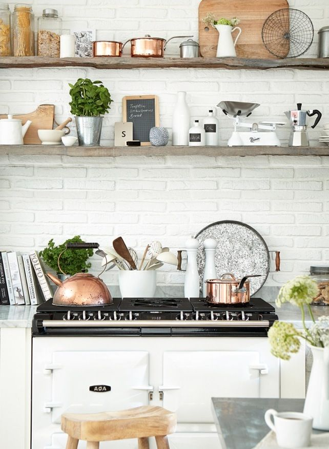 Floating shelves made from distressed planks hang over a white kitchen. Lined with copper and ceramic accessories, they bring a touch of farmhouse chic to the scheme. Photography: Mark Scott