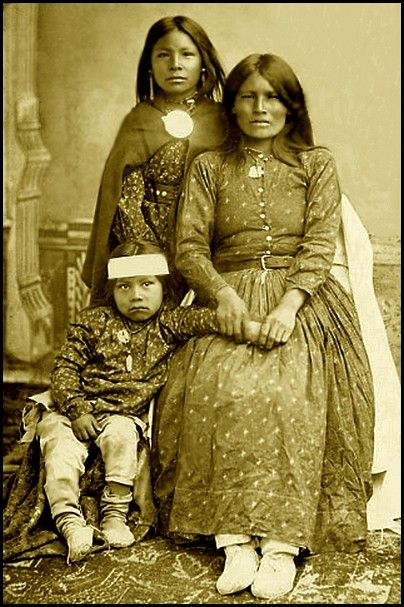 Portrait of Chiricahua woman, Neschila (The Woman Who Winks), Natches' Mother, and two children. Photographed 1881. National Anthropological Archives, Smithsonian Institution.