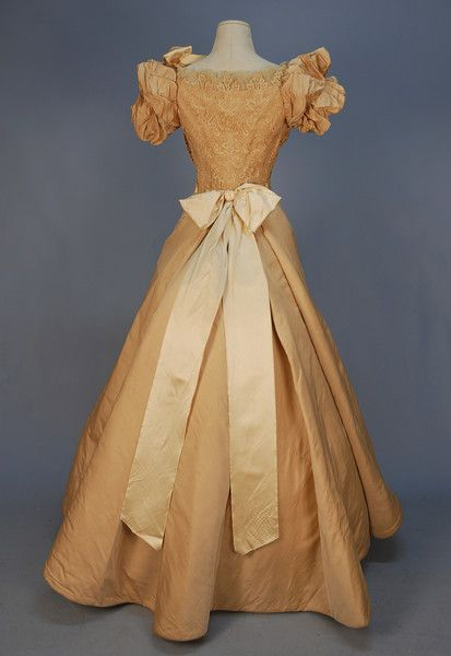 """LONDON MAKER SILK and LACE EVENING GOWN, LATE 1860's. Ivory bengaline with short ruched and puffed sleeve, the boned bodice with inside front closing corset and side hook & eye closures, covered in guipure with pleated chiffon and satin ribbon trim, plain gored skirt. Petersham stamped """"Robes Miss L. Lake 58 Halsey St."""" with crown"""
