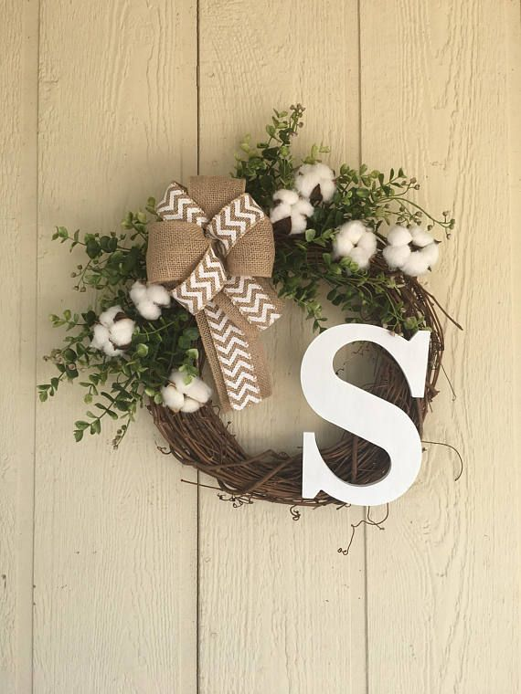 Farmhouse style front Door Wreath featuring greenery and cotton boll accents for a simple and natural look. Greenery includes Eucalyptus and Beach Basswood stems. Personalized with Initial of your choice painted white to bring out the cotton and chevron ribbon. Great addition to