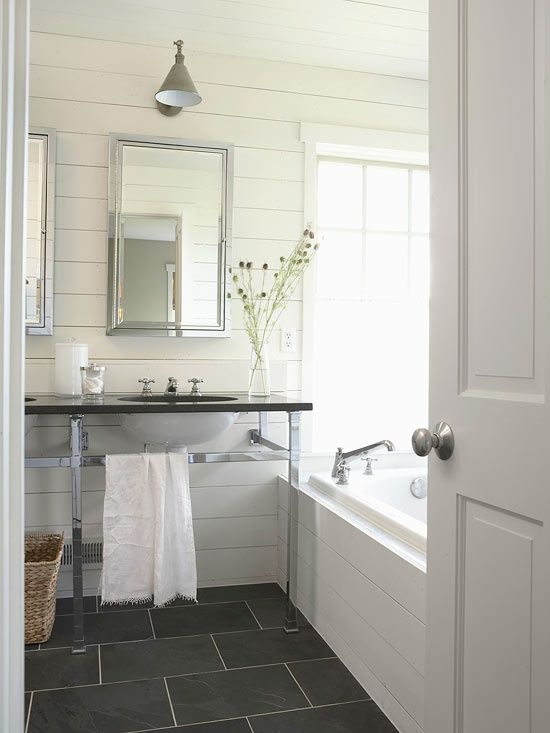 bathroom for the basement - gray slate tiled floor plank board horizontal walls bath surround modern double sink washstand chrome legs black countertop framed medicine cabinet industrial wall sonce white.