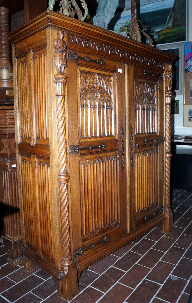 Een eikenhouten 2-deurs legkast voorzien van neogothisch snijwerk in de vorm van o.a. spitsbogen, rozetten en ridders