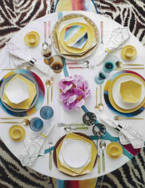 There's a lot going on here: Every place setting has different stemware; there seems to be a random mix of chargers and plates, as well as flatware.  This entire table seems to be pulled together by the graphic tablecloth and napkins.  Impressive.
