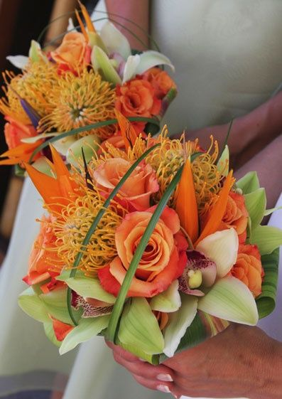 Pincushion protea, green cymbidium orchids, birds of paradise and orange roses, with greenery.