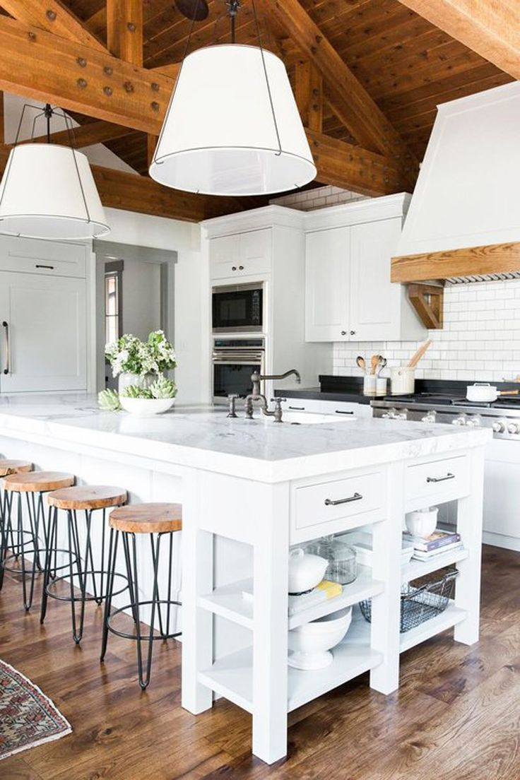 White kitchen with warm wood planked ceiling and oversized pendant lights