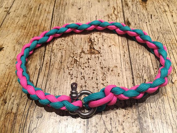 A pink and teal/turquoise rope style tag collar, 0.5 (half an inch) wide. Made of braided 550 paracord for strength and durability with a nautical screw clasp fastening to hold the collar securely closed. The clasp unscrews, making it easy for you to add your dogs ID tags to the collar without fighting with stubborn split rings. Each collar is hand made to measure - please measure your hounds neck where youd like the collar to sit. The tape measure should touch the neck all the way aroun...