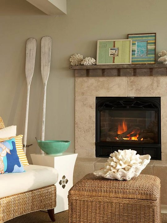 Love this beachy fireplace with the rowing oars & striped frames via BH&G