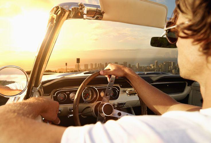 Caucasian man driving convertible towards cityscape - Caucasian man driving…