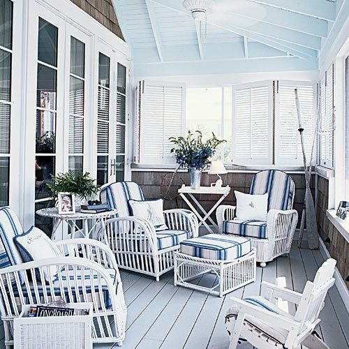 a side sunroom porch with a pale blue ceiling and white walls surround white wicker chairs with navy striped over-stuffed cushions