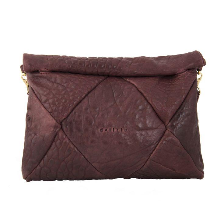 El bolso Duae es de color burdeos. El cierre es de imanes, sin cremallera. de algodón, gris claro y contiene un bolsillo con cremallera.