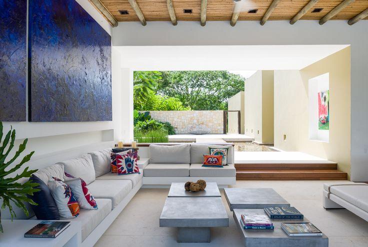 """Un sofá bajo de mampostería en """"L"""" y un díptico azul realzan el aspecto de la sala en la que predominan el blanco y el gris pizarra."""