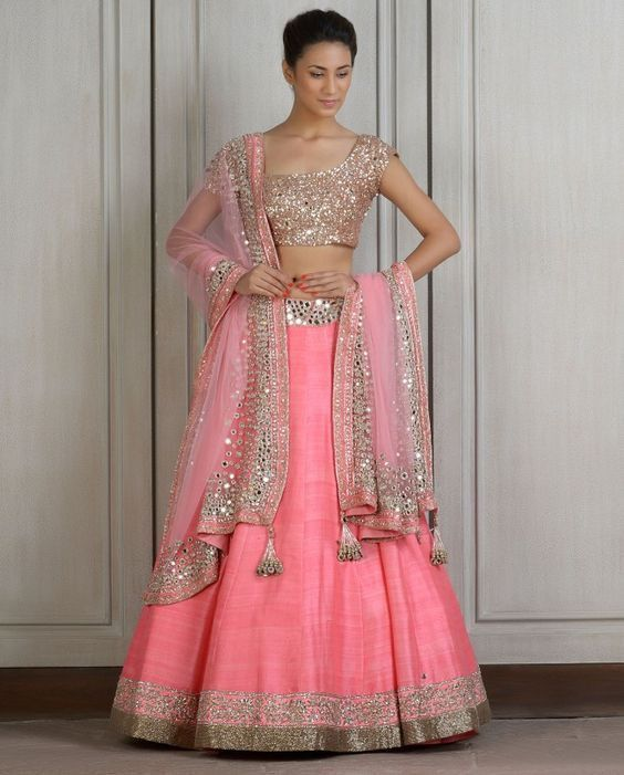 Raw silk baby pink Lehenga. Mirror work on the borders of Lehenga and dupatta. Comes with mirror workcholi.