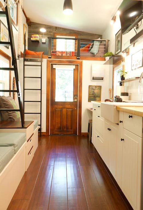 The 144 sq.ft. tiny house includes a queen size loft and a single sleeper loft, kitchen with mini fridge and two burner stove, living room, bathroom, and an outdoor deck.