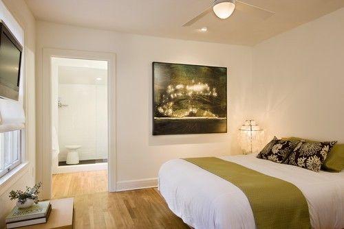 Dieser weiß getünchten Hauptschlafzimmer stützt sich auf seinen hölzernen Bodenbelag für einen Hauch von Wärme und gemütliche Ausstrahlung. Foto von Texas Baufirma