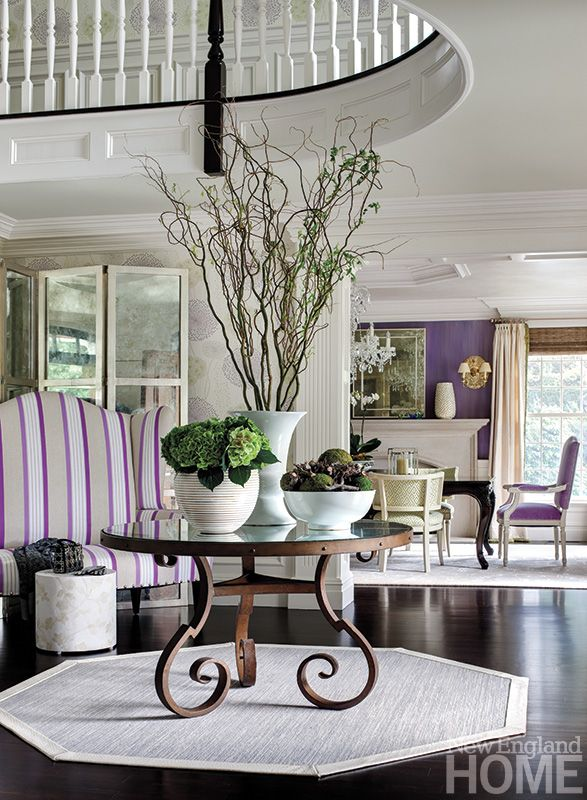 """The foyer was an opportunity to do something dramatic and unexpected and to reflect the energy level throughout the house,"" says designer Gerald Pomeroy, who accomplished his aim with an oversize striped banquette, playful wallpaper, a mirrored screen and a circular console table. Strong architectural details balance out the space."
