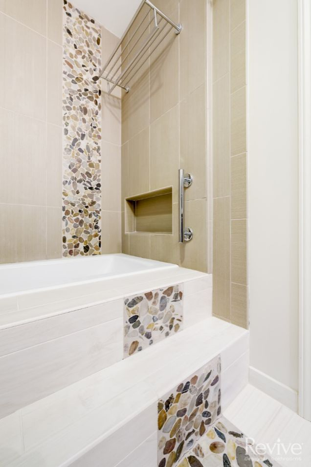 This shower features a custom niche within the wall for storage, as well as a shelf and towel rod.