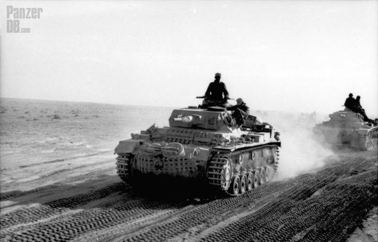 https://flic.kr/p/uY83kE | Panzerkampfwagen III (5 cm Kw.K. 38 L/42) Ausf. G Tp (Sd.Kfz. 141) | Un Panzer III Ausf. H sur une piste d'Afrique du Nord, probablement en Cyrénaïque.  Le mode de fixation des patins de chenilles de rechange est encore effectué via les crochets avant de remorquage. Il disparaîtra ensuite par l'adjonction d'une barre métallique horizontale sur le glacis avant. Les roues de routes supplémentaires, déposées sur les maillons de chenilles, seront alors placés sur le…