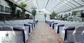 Purple and white wedding ceremony decor, ceremony aisle decor, chair sashes along aisle, chair sashes with flowers, aisle rose petals, pedestals with floral arragements, atrium wedding ceremony, trpoical wedding ceremony