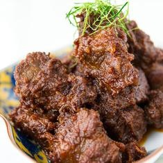 Beef Rendang   West Sumatra caramelized beef curry   Beef is slowly simmered with coconut milk and a mixture of lemongrass, galangal, garlic, turmeric, ginger and chilies, then left to stew for a few hours to create this dish of tender, flavorful bovine goodness.