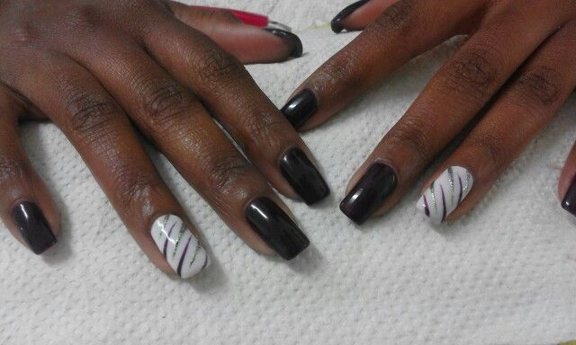 Dark purple gel with one nail white gel finished off with free hand purple & silver strokes